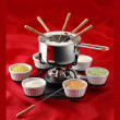 Fondue on red background — Stock Photo