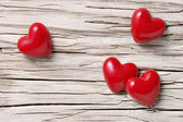 Four hearts on white wood — Stock Photo