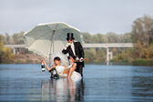 Bride and groom is happy in the river — Stock Photo