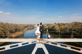 Bride and groom on bridge over the river — Stock Photo