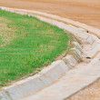 Ditch between green football ( soccer ) field and racetrack — Stock Photo
