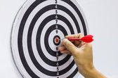 Hand and red dart on dartboard — Stock Photo