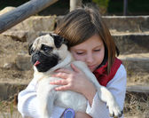 Children with her pug dog — Stock Photo