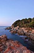 Sunrise on a beach full of rocks — Stock Photo