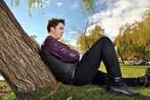 Young man sitting on a park — Stock Photo
