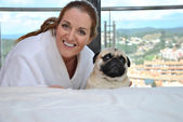 Happy woman with her pug dog — Stockfoto