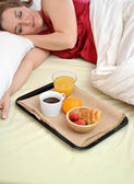 Woman sleeping on her bed with a breakfast at his side — Stock Photo