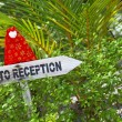 Wooden pointer to reception of a tropical hotel — Stock Photo