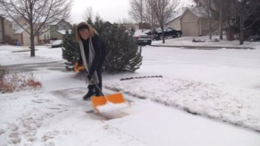 Woman shoveling snow — Stockvideo