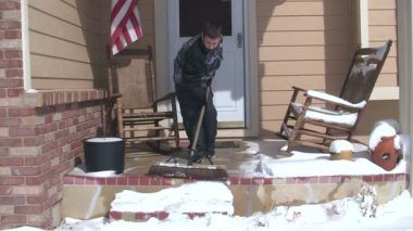 Boy sweeping snow from porch — Стоковое видео
