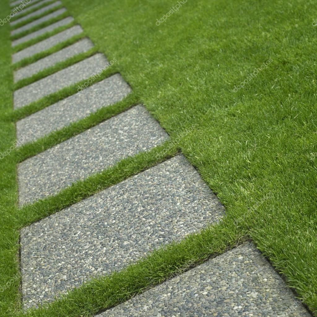 Cuidado c sped y baldosas de piedra foto de stock for Bloques de cemento para pisos de jardin