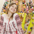 Foto Stock: Nice smiling girl are standing on backgroung of Easter Eggs