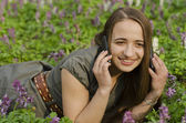Beautiful girl is lspeaking on mobile in corydalis — Stock Photo