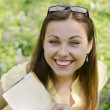 Stock Photo: Portrait of beautiful smiling girl with book and glasses in spri