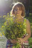 漂亮的女孩在夕阳光举行花 (金凤花 — 图库照片