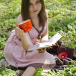 Stock Photo: Beautiful smiling girl with book is holding red ornamented cup