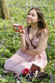 Beautiful smiling girl is holding red ornamented cup — Stock Photo