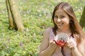 Beautiful smiling girl is holding cup with strawberries — Stock Photo
