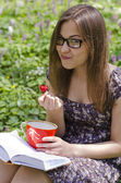 Smiling beautiful girl in glasses is eating strawberry — Stock Photo