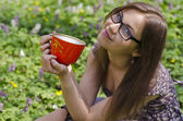 Smiling beautiful girl in glasses is holding red cup — Stock Photo