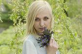Portrait of beautiful blonde girl with lungwort flowers on willo — Stock Photo