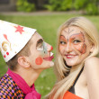 Portrait of man dressed like a clown trying to kiss a girl with butterfly makeup — Foto de Stock