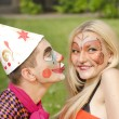 Portrait of man dressed like a clown trying to kiss a girl with butterfly makeup — Stock fotografie