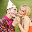 Portrait of a smiling man dressed like a clown trying to present a flower to a happy girl with butterfly makeup — Stock Photo #29571021