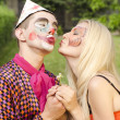 Portrait of man dressed like a clown trying to kiss a girl with butterfly makeup — Stock Photo #29571035