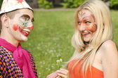 Portrait of man dressed like a clown trying to present a flower to a girl with butterfly makeup — Stock Photo