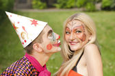 Portrait of man dressed like a clown trying to kiss a girl with butterfly makeup — Stock Photo
