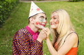 Portrait of a smiling man dressed like a clown trying to present a flower to a happy girl with butterfly makeup — Stock Photo