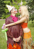 Portrait of a smiling man dressed like a clown presented a balloon to a happy girl with butterfly makeup — Stock Photo