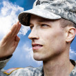 Saluting Army soldier on the blue sky background - Stock Photo