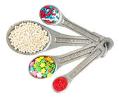 Measuring spoons with different kinds of cookie sprinkles isolat — Stock Photo