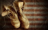 US Army boots on the old paper flag. 4th of july background — Stock Photo