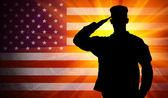 Soldado orgulhoso exército masculino de continência no fundo da bandeira americana — Fotografia Stock