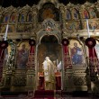 Orthodox iconostasis and priest — Stock Photo