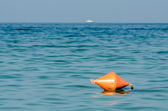 Orange Life Buoy In Ocean With Ship In Sight — Stock Photo