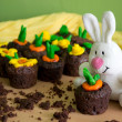 Chocolate muffins with fondant decorations in the shape of flowers and vegetables in spring brilliant colors and white plush rabbit — Foto Stock