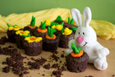 Chocolate muffins with fondant decorations in the shape of flowers and vegetables in spring brilliant colors and white plush rabbit — Zdjęcie stockowe