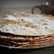Crepe cake layered with chocolate pudding and jam, sprinkled with powdered sugar with cups in the background — Stock Photo #26889707