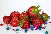 Verse rode aardbeien met groene stengels en gekleurde kralen op een witte achtergrond — Stockfoto