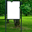 White board on poles in a park surrounded by greenery — Stock Photo