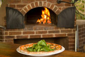 Pizza on a plate with pizza oven in background — Stock Photo