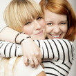 Stock Photo: Red and blond haired girls laughing and hug