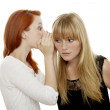 Young beautiful red and blond haired girls telling a secret — Stock Photo