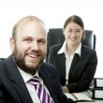 Beard business man brunette woman at desk smiling — Stock Photo #20756885