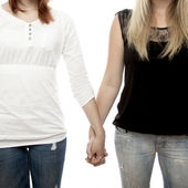 Young beautiful red and blond haired girls holding hands close up — Stock Photo