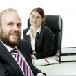 Beard business man brunette woman at desk smile — Stock Photo